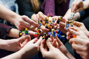 people holding miniature figures