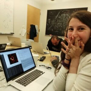 Katie Bouman with the first image of a black hole displayed (using Python!) on her laptop.