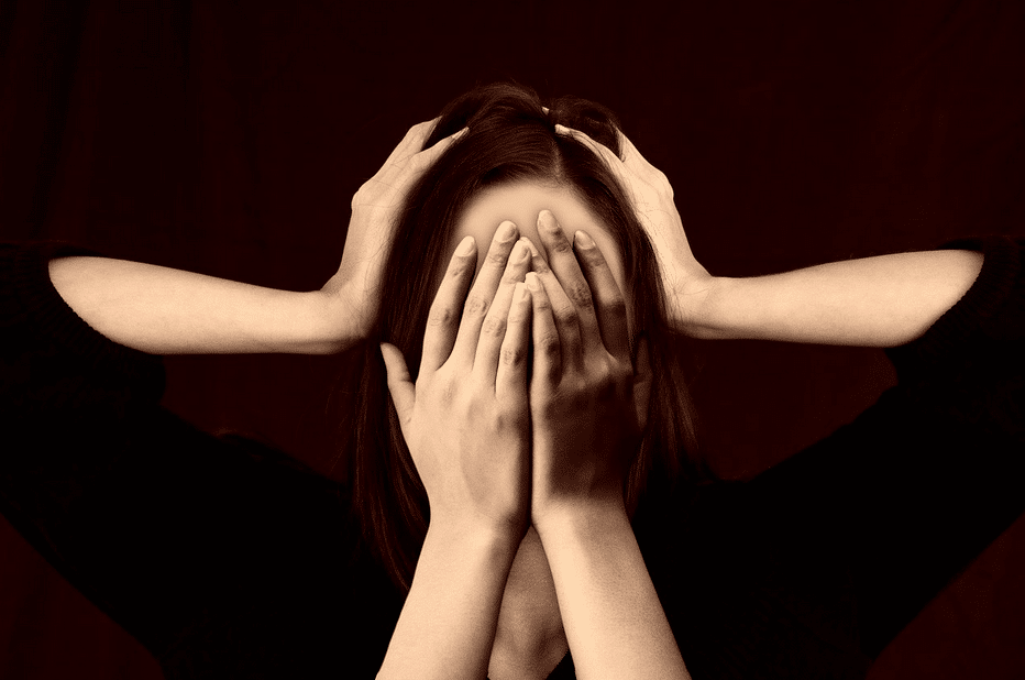An image of a woman with her hands over her face.