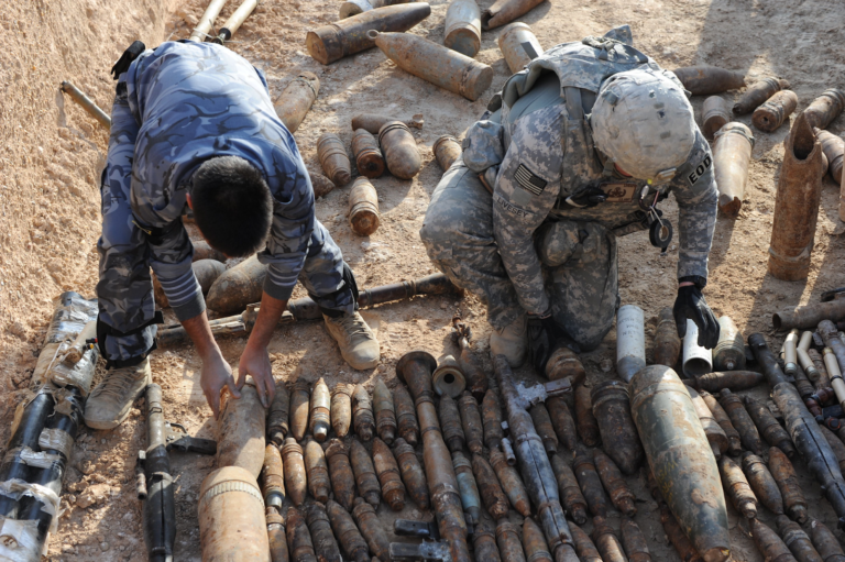 Military personnel handling unexploded ordnance.